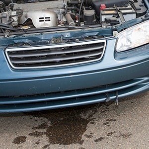 Coolant leak on the ground underneath a car with the hood up