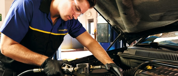 Goodyear service technician using a filler during an oil change service