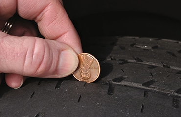 Checking a tire's tread depth using the penny test method